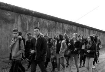 Berlin  Deutschland  Jugendliche laufen an einem Teil der ehemaligen Grenzmauer vorbei