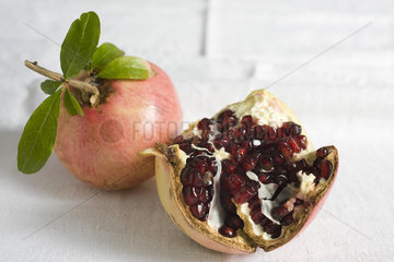 Fresh pomegranates  one cut open revealing seeds