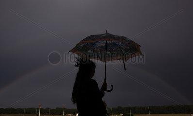 Hoppegarten  Deutschland  Silhouette  Frau mit Regenschirm steht vor einem Regenbogen