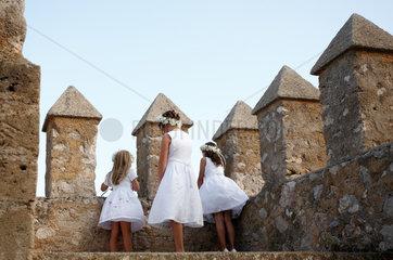 Arta  Mallorca  Spanien  Blumenkinder blicken ueber die Festungsmauer