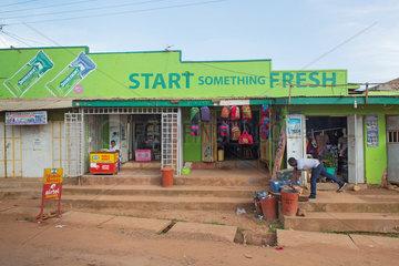 Wakiso Town  Uganda - Strassenszene. Ladengeschaefte mit Kaugummireklame