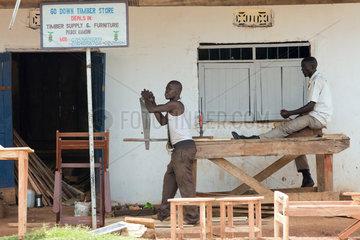 Kamdini  Uganda - Tischlerei. Ein Schreiner saegt mit einer Holzsaege ein Holzbrett laengst.