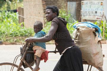 Kamdini  Uganda - Stadtansicht. Eine Frau schiebt ein Fahrrad mit einem Kleinkind und einem Sack auf dem Gepaecktraeger.