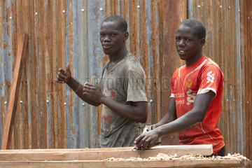 Kamdini  Uganda - Ein Schreiner hobelt mit einem Holzhobel einen Holzbalken.