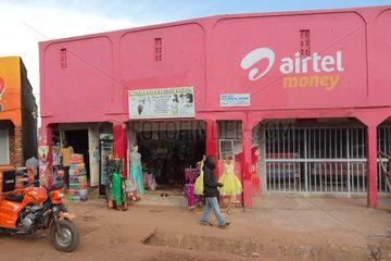Wakiso Town  Uganda - Strassenszene. Ladengeschaefte. Ein Mann laeuft an einer pink farbigen Frauen-Boutique vorbei.