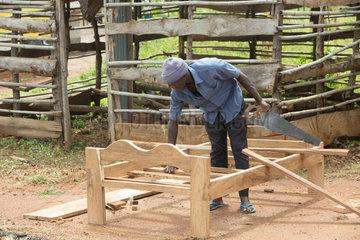 Kamdini  Uganda - Ein Schreiner tischlert ein Holzbett am Strassenrand.
