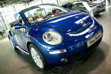 Wolfsburg  Deutschland  Besucher schauen sich einen New Beetle in der Autostadt an