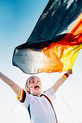 Boy  enthusiastic for soccer world championship  waving German flag