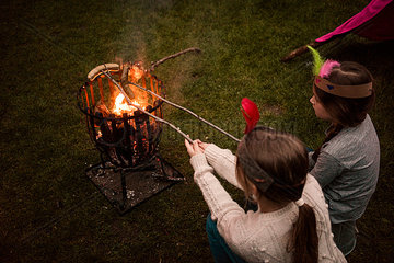 Two girls wearing feather headdress  grilling sausage over camp fire