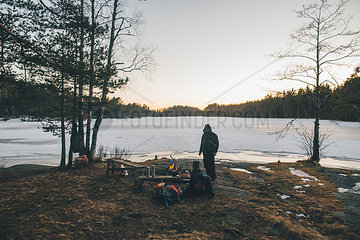 Sweden  Sodermanland  backpacker resting at a remote lake in winter
