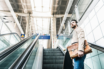 Young man with skateboard and headphones on escalator at the station