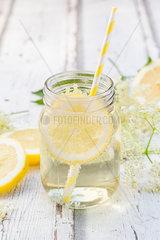 Glass of homemade elderflower sirup with slices of lemon