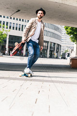Young man with guitar riding skateboard in the city