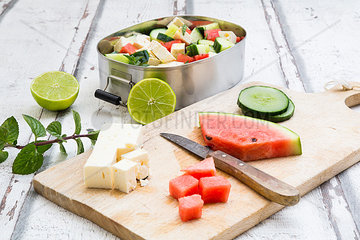 Lunch box  preparation of watermelon salad with feta  cucumber  ment and lime dressing