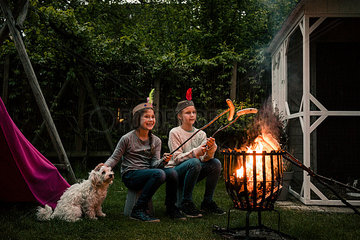 Two girls wearing feather headdress  grilling sausage over camp fire  dog sitting on meadow