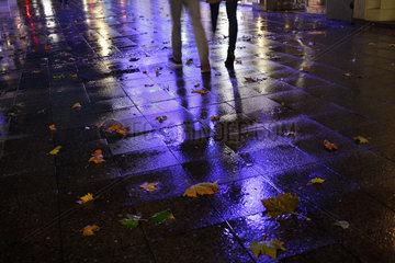 Berlin  Deutschland  Passanten und Lichtreflexe auf dem nassen Gehweg