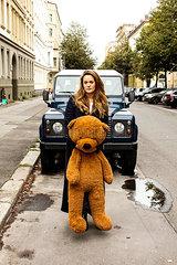 Junge Frau mit Teddy Baer auf Strasse vor Auto