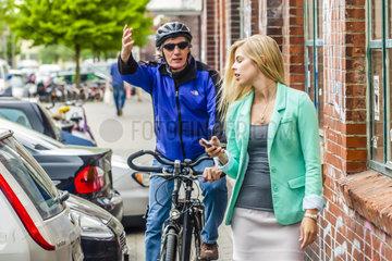 Radfahrer versucht sich auf sehr engem Fussweg an Fussgaengerin vorbei zu draengeln