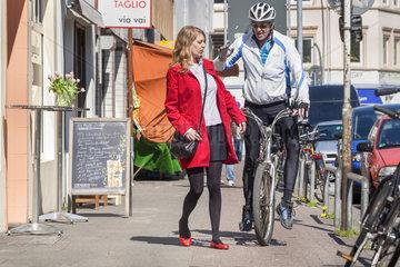 Unachtsame junge Fussgaengerin stoesst beim ueberqueren des Fahrradweges mit einem fahrradfahrer fast zusammen