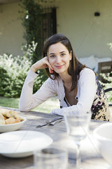 Woman at gathering of friends for meal outdoors