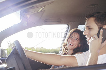 Couple riding in car together while driver chats on cell phone without hands-free device