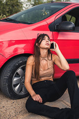 Young woman sitting at roadside having a car breakdown calling breakdown service
