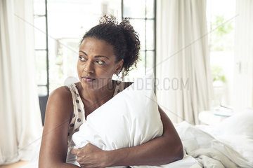 Woman hugging pillow on bed  portrait