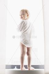 Baby standing by window  looking over shoulder