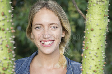 Young woman smiling cheerfully outdoors  portrait