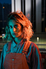 Portrait of a beautiful woman at night  wearing dungarees