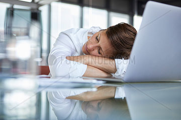 Businesswoman with closed eyes lying on glass table in office in front of laptop