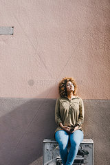 Woman sitting in front of house wall  enjoying the sun