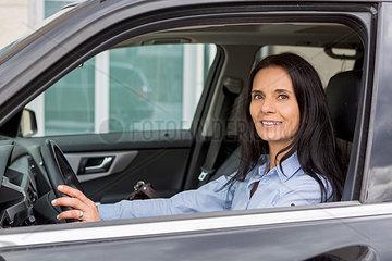 Portrait of smiling woman driving car