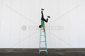 Acrobat balancing upside down on a ladder