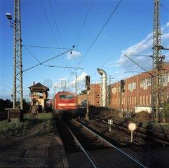 Roter Zug verlaesst Bahnhof im Abendlicht