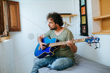 Spain  Man playing bass guitar in his room
