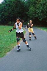 Zwei junge Maedchen fahren auf Roller skates