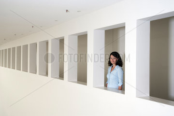 Freiburg  Deutschland  eine junge Businessfrau steht in einem Fenster