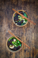 Two bowls of Japanese miso soup with sugar peas  shitake mushrooms  tofu and mung sprouts