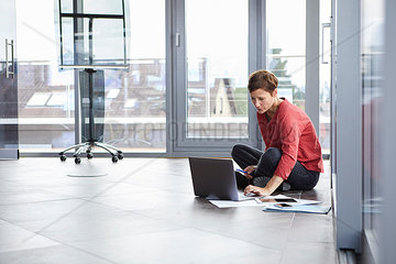 Businesswoman sitting on the floor in office using laptop