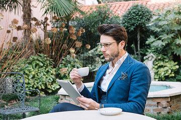 Elegant businessman using tablet in a garden cafe