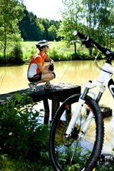 A cycling woman taking a break at a lake