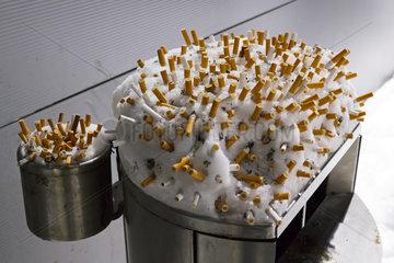 Berlin  Deutschland  Zigaretten stecken in der Schneehaube eines Muelleimers