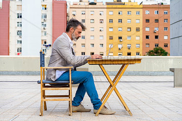 Businessman sitting on roof terrace working on laptop