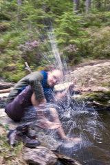 Mann spritzt mit Wasser
