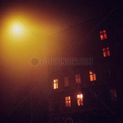 Berlin  Deutschland  beleuchtete Fenster in einem Altbau bei Nacht und Nebel