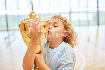 Blonder Junge kuesst einen Sieger Pokal