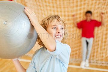 Junge wirft einen Gymnastikball