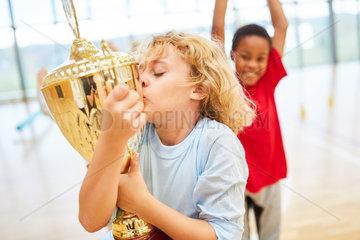 Gluecklicher Junge kuesst einen Pokal