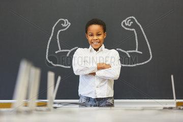 Afrikanisches Kind vor Tafel mit Muskeln